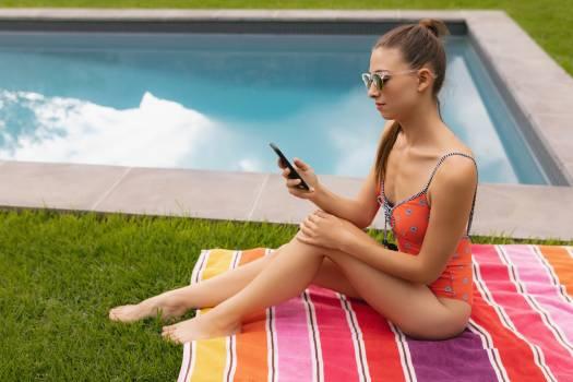 Woman in swimwear using mobile phone poolside in the backyard #417744