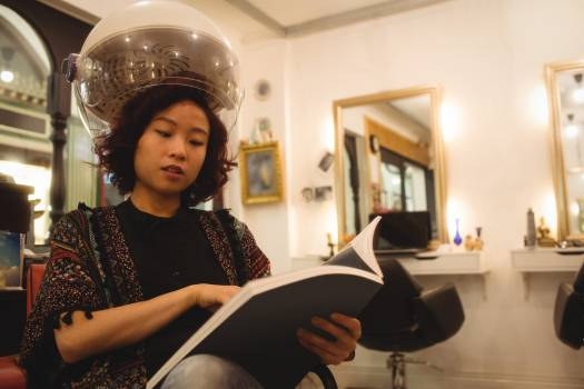 Stylish woman reading a magazine while sitting under a hairdryer Free Photo