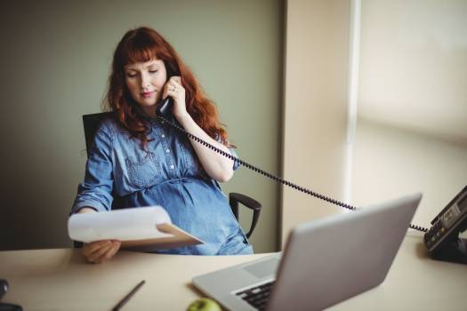 Pregnant businesswoman talking on telephone while working #417858