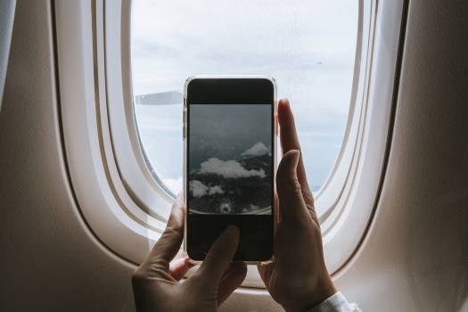 Woman capturing clouds from the plane window with her phone #417947