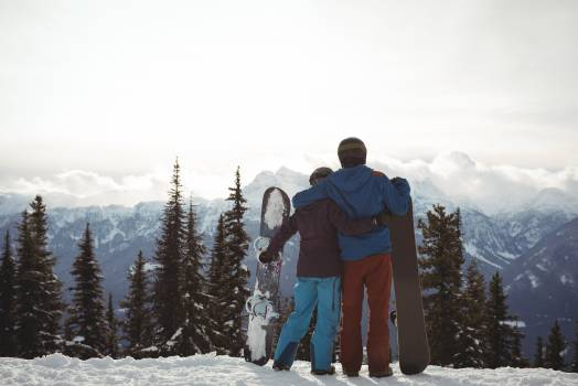 Rear view of couple holding snowboard at mountain during winter against sky #418162