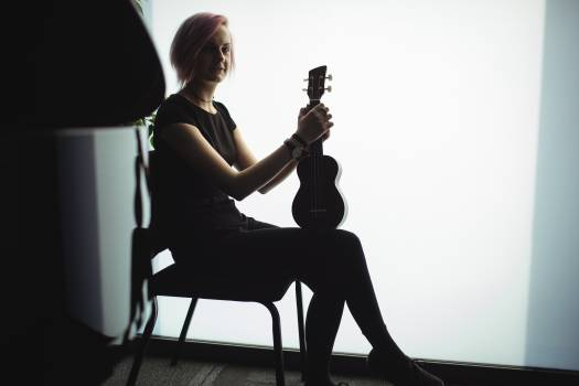 Woman sitting with a guitar in music school Free Photo