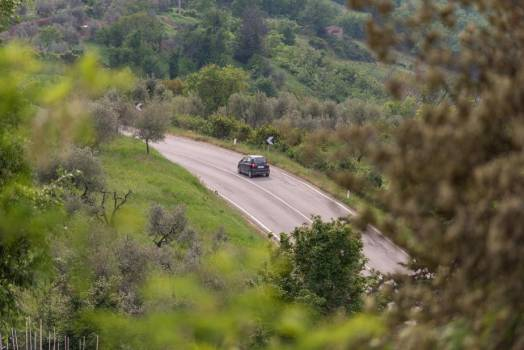 A Car Winds Round A Curve On A Highway On A Hill #418333