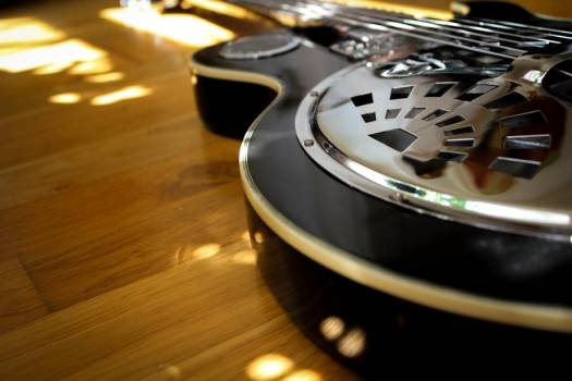 A Black Guitar Reflects Sunlight Onto The Wooden Floor #418348