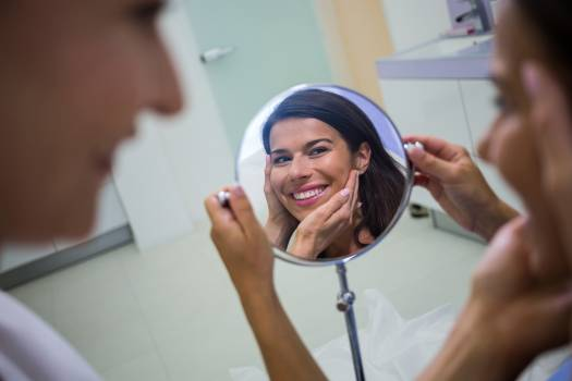 Woman checking her skin in the mirror after receiving cosmetic treatment Free Photo