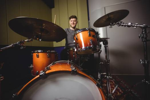 Male student playing drum set Free Photo