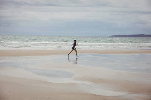 Athlete running along the beach Free Photo