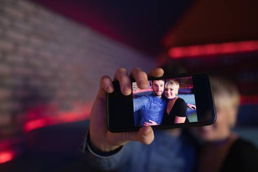 Couple taking selfie on mobile phone in bar Free Photo