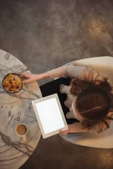 Woman with digital tablet having breakfast at home Free Photo