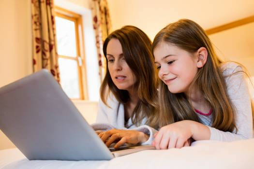 Mother and daughter using laptop in bedroom #418900
