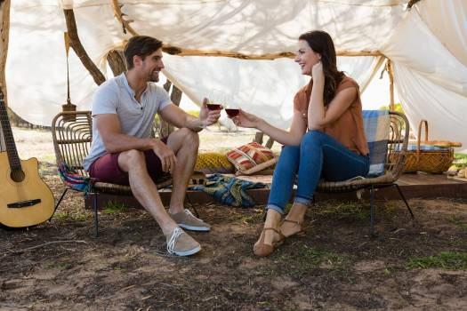 Full length of couple toasting wine in tent Free Photo