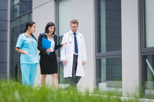 Doctors and nurse interacting while walking Free Photo