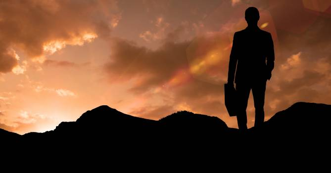 Silhouette businessman standing on mountain during sunset Free Photo