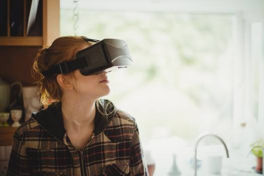 Woman experiencing virtual reality headset in kitchen Free Photo