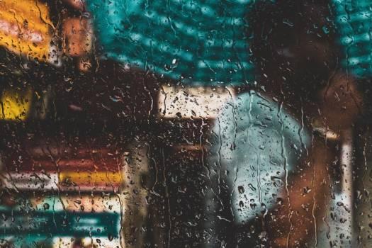 A Person With An Umbrella Through A Rain-Speckled Window #419420
