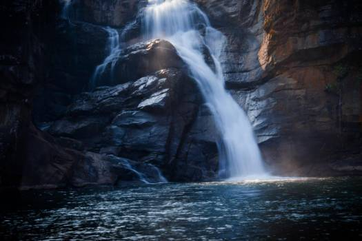 A Waterfall Over Rocks Into The Lake Below #419431