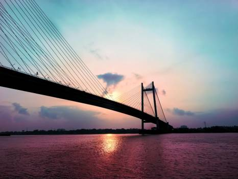 A Suspension Bridge Silhouetted By Sunset #419439