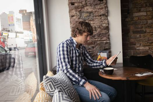 Man using digital tablet while having coffee Free Photo