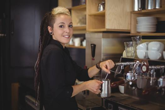 Portrait of smiling waitress using the coffee machine  #420103