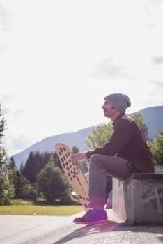 Man with skateboard sitting in skate park #420190