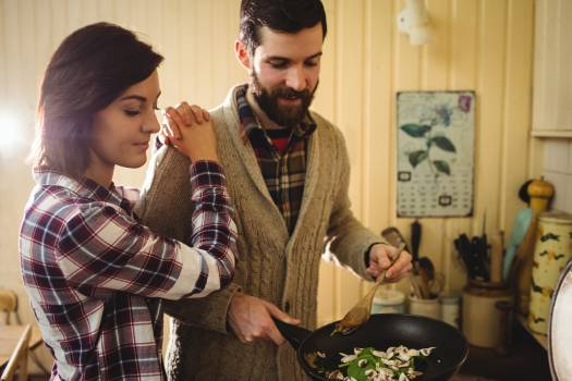 Couple preparing food together in kitchen Free Photo