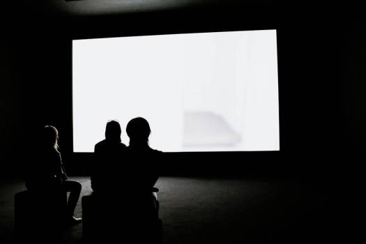 Three Woman Watch A Glowing White Screen In a Dark Room #421311
