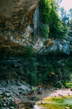 Hikers Under A Rocky Outcrop And Small Waterfall #421926