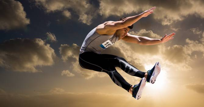 Athlete jumping in air against cloudy sky #422156