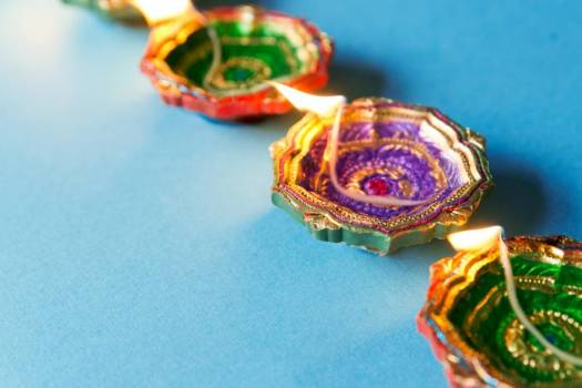 Several Diya Lamps Sit Aflame A Blue Background #422480