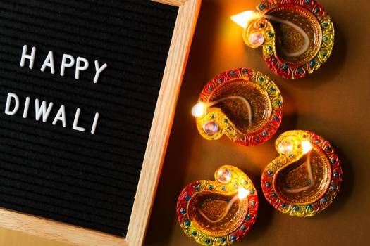 Happy Diwali Sign Laying Beside Four Diya Lamps #422482