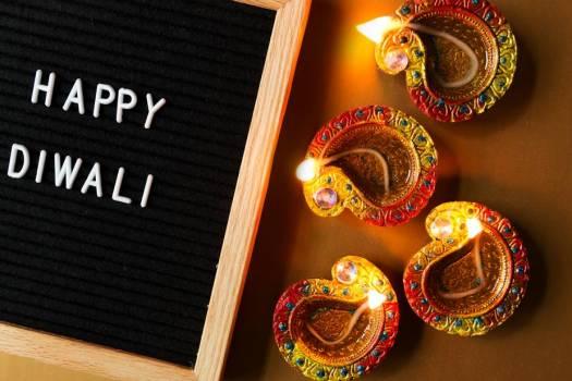 Happy Diwali Sign Laying Beside Four Diya Lamps #422482