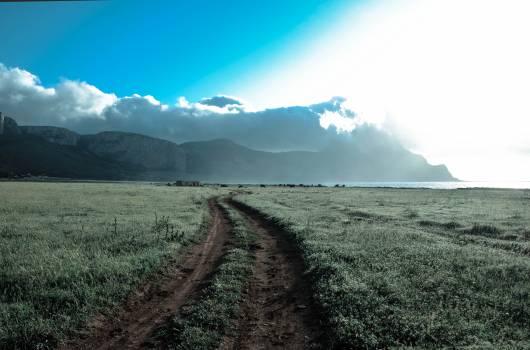 Green Grass Field Beside Brown Mountains Under White Cloudy Sky #42439