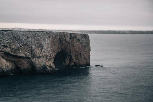 A Cave Gulps In Icy Water Out The Side Of A Cliff #424549