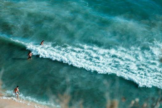 Bathers Wade Into Turquoise Waters Off A Sandy Beach #424560