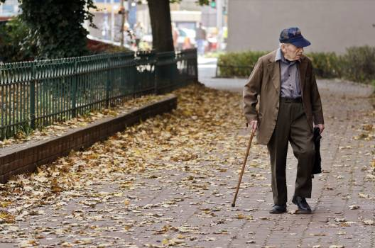 Photo of Elderly Man Walking on Pavement #424887