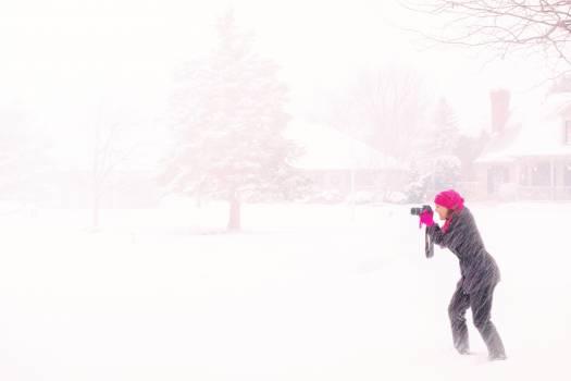 Woman in Pink Hijab Holding Black Dslr Camera Under Raging Snow during Daytime #42501