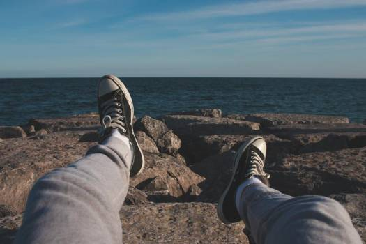 Feet In Sneakers Pointed Towards Open Ocean Off Rocky Shore #425264