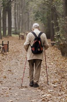 Man Carrying Backpack While Walking on a Paved Pathway #426477