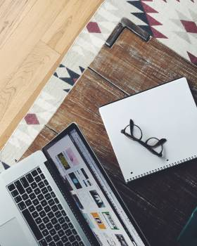 Black Frame Eyeglasses on Top of White and Black Spiral Notebook Beside Macbook Pro on Brown Wooden Table #42973