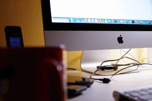 Silver Imac Turned on Beside Red Ceramic Cup #43457