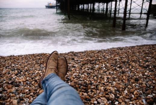 Person Wearing Blue Denim Pants and Brown Boots Sitting on Brown and Black Stone in Front of Body of Water #43742