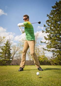Man in Green and White Stripes Long Sleeve Shirt Holding Black Golf Club Free Photo