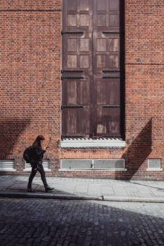 Woman in Black Jacket and Black Pants Walking Along the Road Near the Brown Bricked Building Free Photo