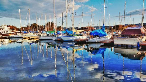 Boats on Dock Reflecting on Water during Daytime Free Photo