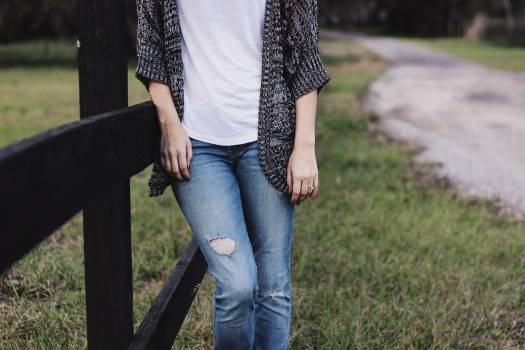 Woman in Blue Distressed Denim Jeans Grey Tank Top and Black Blazer Leaning on Brown Wooden Fence Free Photo