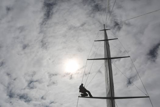 Man Climbing on Top of Structure Under White Clouds during Daytime Free Photo