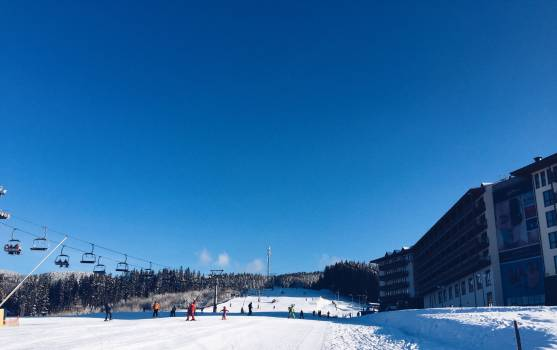 People on a Snowy Ski Hill With a Lift on the Left and a Hotel on the Right Free Photo