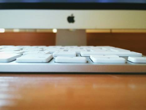 White Computer Keyboard on Brown Wooden Table Free Photo