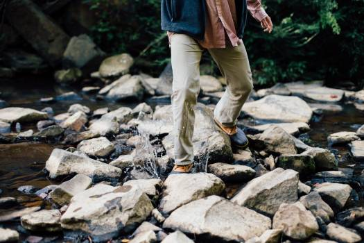 Man Trekking Rocky Stream during Daytime Free Photo