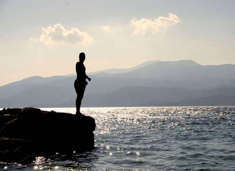 Person Standing on Rock Besides Sea Near Island during Daytime #44991